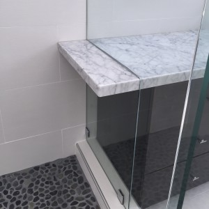 master bath details. carrera marble extends from the counter top into the shower stall.