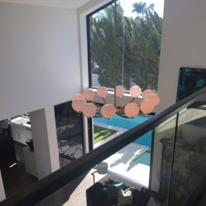 view from the top of the stairs, across the sunny living room, and out to the pool