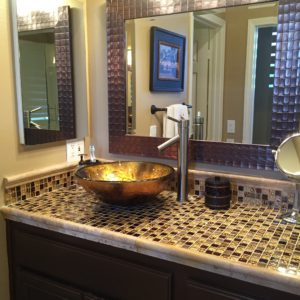 the master bath had two separate opulent tile countertops with gold vessel sinks.