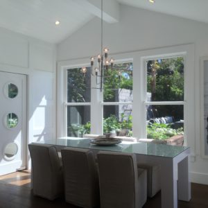 dining room with a view of the backyard. fun porthole pantry door on the left